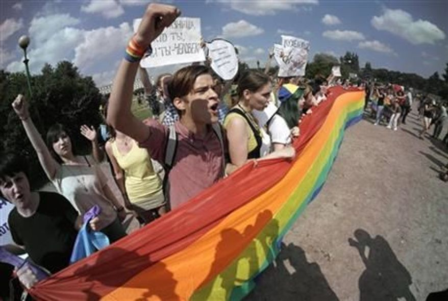 Gay rights activists shout slogans during their authorized rally in St.Petersburg, Russia, Saturday, June 29, 2013. Police detained several gay activists, who were outnumbered by the protesters. Dozens of gay activists had to be protected by police as they gathered for the parade, which proceeded with official approval despite recently passed legislation targeting gays. (AP Photo/Dmitry Lovetsky)