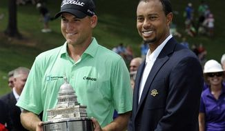 Bill Haas, left, poses with Tiger Woods after winning the AT&T National golf tournament at Congressional Country Club, Sunday, June 30, 2013, in Bethesda, Md. (AP Photo/Nick Wass)
