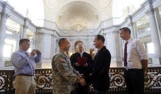 Army Capt. Michael Potoczniak (second from left) and Todd Saunders (second from right) of El Cerrito, Calif., are married by Deputy Marriage Commissioner John Loschmann (center) as witnesses Bill Hershon (left) and Sean Boileau look on at City Hall in San Francisco on Saturday, June 29, 2013. (AP Photo/Marcio Jose Sanchez)