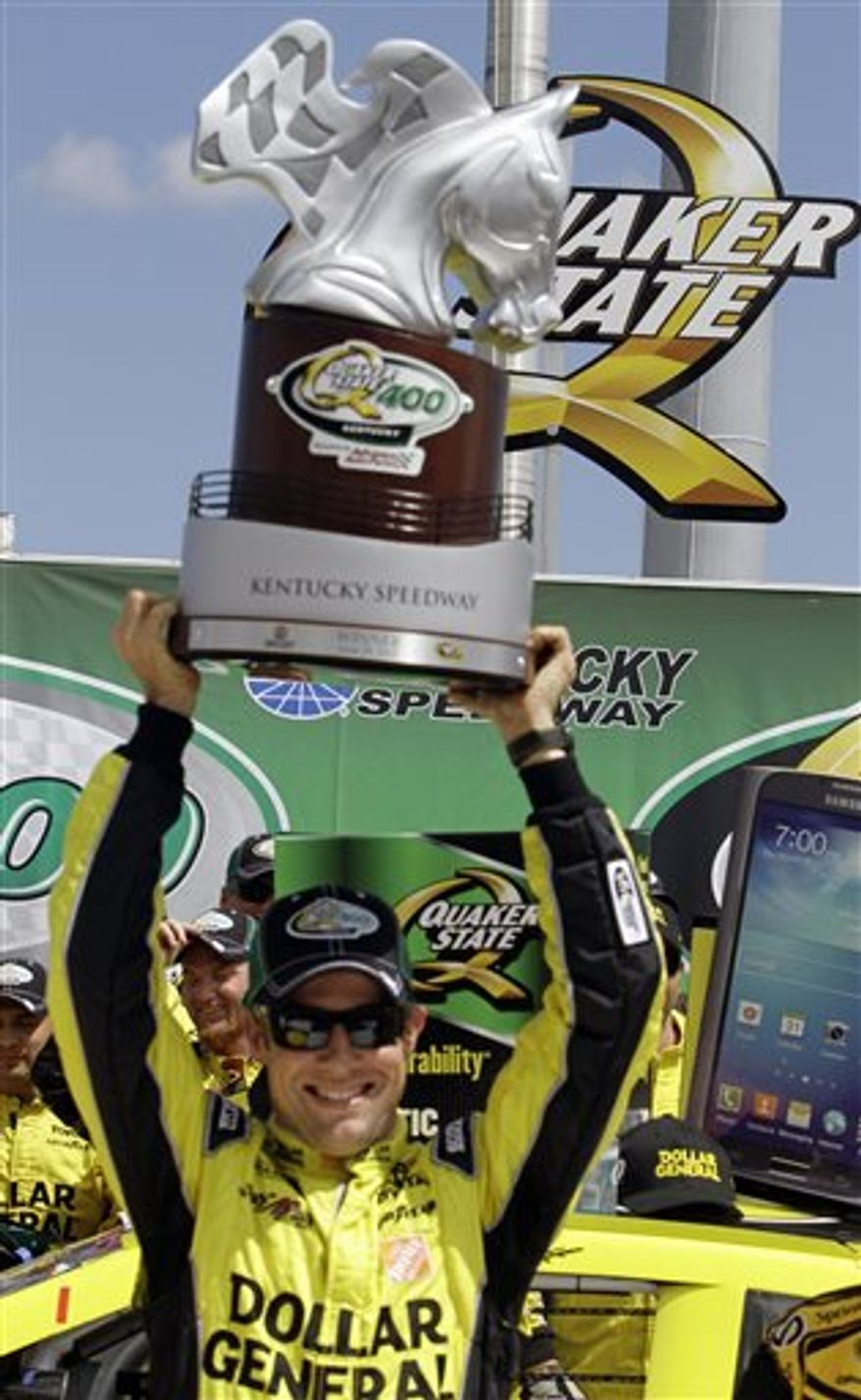 Matt Kenseth celebrates his victory in the NASCAR Sprint Cup auto race at Kentucky Speedway in Sparta, Ky., Sunday, June 30, 2013 by hoisting the trophy above his head in the winner's circle. (AP Photo/Garry Jones)