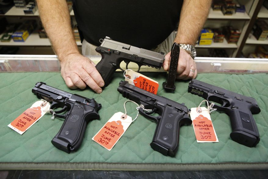 Richard Taylor, manager of the Firing-Line gun store in Aurora, Colo., displays on Thursday, June 27, 2013, some of the pistols that he won't be able to sell after June 30 because their magazines hold more than 15 rounds. (AP Photo/Ed Andrieski)