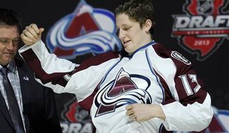 Nathan MacKinnon, a center, pulls on a Colorado Avalanche sweater after being chosen 1st overall in the first round of the NHL hockey draft, Sunday, June 30, 2013, in Newark, N.J. (AP Photo/Bill Kostroun)