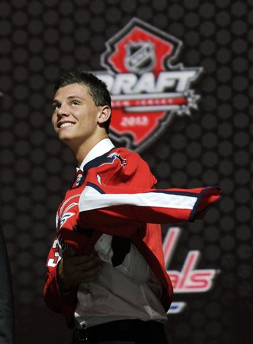 Andre Burakovsky, a winger, pulls on a Washington Capitals sweater after being chosen 23rd overall in the first round of the NHL hockey draft, Sunday, June 30, 2013, in Newark, N.J. (AP Photo/Bill Kostroun)
