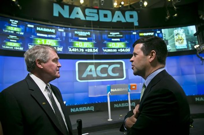 Atlantic Coast Conference commissioner John Swofford, left, and NASDAQ head of listings Bob McCooey chat before the ringing of the closing bell on Monday, July 1, 2013 in New York. The ACC visited the NASDAQ Market Site in Times Square to officially announce the addition of its three new members in Notre Dame, Pitt and Syracuse. (AP Photo/Bebeto Matthews)