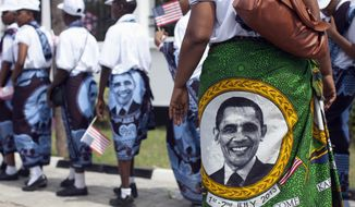 Young girls and women wear khangas, a traditional wrap, with the image of U.S. President Barack Obama as they line up to enter the State House, in Dar es Salaam, Tanzania, Monday, July 1, 2013, to greet and perform for U.S. President Barack Obama and first lady Michelle Obama. (AP Photo/Carolyn Kaster)
