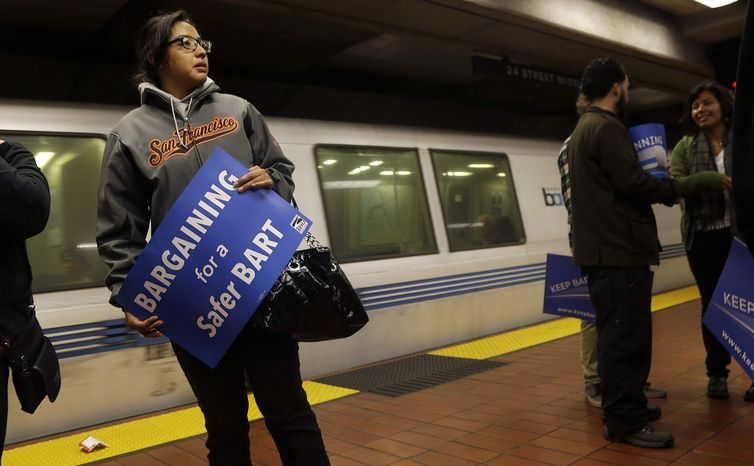 ** FILE ** In this Tuesday, June 25, 2013, file photo, Jeanette Sanchez holds a sign supporting Bay Area Rapid Transit workers as she waits for a train at the 24th Street Mission station in San Francisco. Early Monday, July 1, 2013, two of San Francisco Bay Area Rapid Transit's largest unions went on strike after weekend talks with management failed to produce a new contract. (AP Photo/Jeff Chiu)