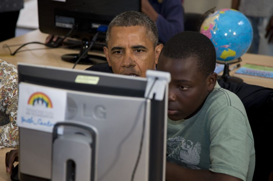President Obama looks at a project prepared by students at the Demond Tutu HIV Foundation Youth Center during his visit to Cape Town, South Africa, on June 30, 2013. (Associated Press)