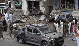Pakistani security officials and rescue workers examine the site of car bombing on the outskirts of Peshawar, Pakistan, Sunday, June 2013. A car bomb exploded as a convoy of paramilitary troops passed through the outskirts of the northwest Pakistani city of Peshawar, killing more than a dozen people and wounding scores of others, police said. (AP Photo/Mohammad Sajjad)