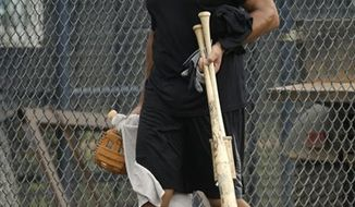 **FILE** New York Yankees third baseman Alex Rodriguez carries his equipment after a workout Wednesday, June 5, 2013, at the Yankees' minor league complex in Tampa, Fla. (AP Photo/Chris O'Meara)