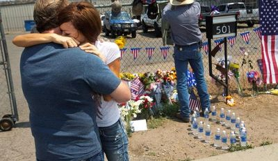 Juliann Ashcraft, whose husband, Andrew Ashcraft, was one of 19 firefighters killed Sunday while battling the Yarnell Hill fire near Prescott, Ariz., hugs her father-in-law, Tom Ashcraft, in front of a memorial at Prescott Fire Station #7 on Monday. The firefighters were trapped by a wildfire that exploded tenfold in a matter of hours and continued to grow.