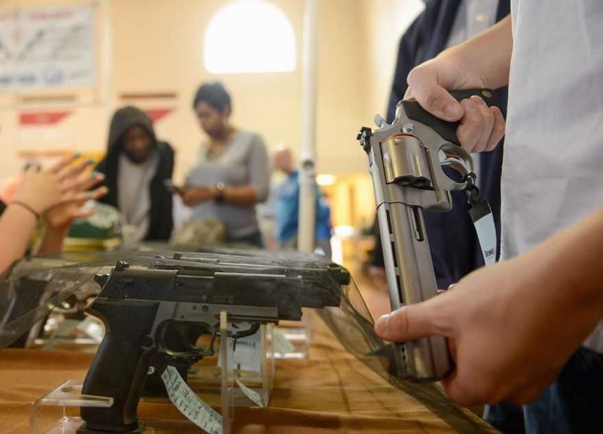 A man examines a handgun at the Annapolis Gun Show in March. June was the first month since October 2011 to see a year-over-year decrease in the total number of FBI instant background checks. (Andrew Harnik/The Washington Times)