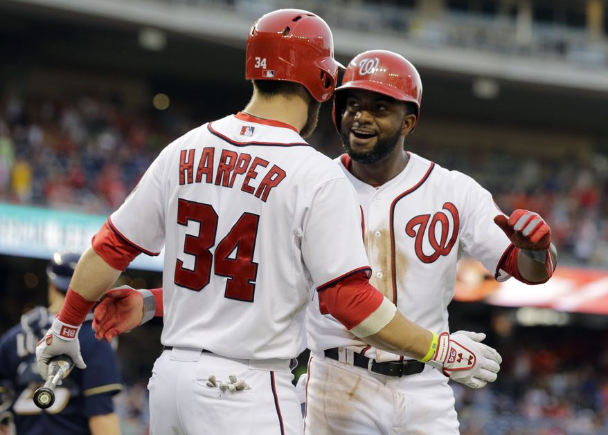 Denard Span, right, celebrates with Bryce Harper after scoring in the Nationals' win over the Brewers on Monday night. (Associated Press photo)