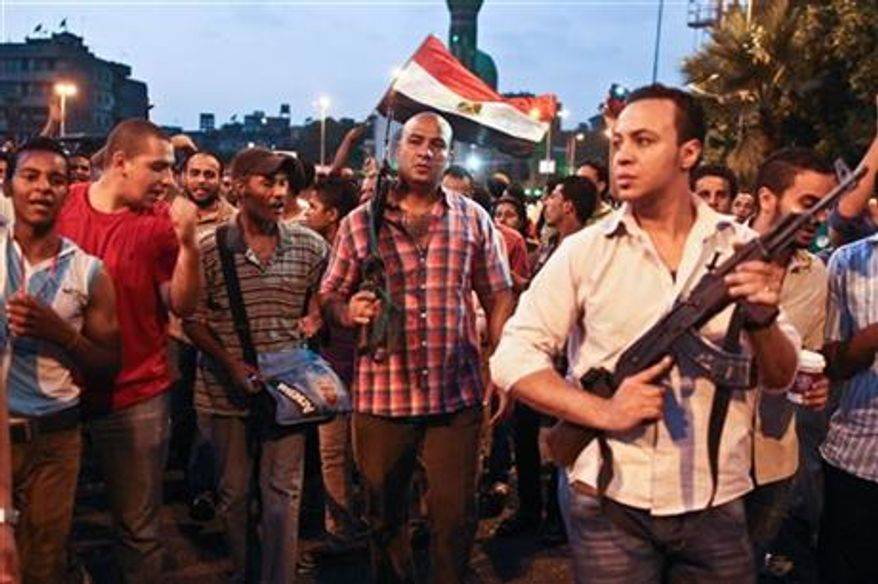 Plainclothes policemen walk with protesters opposed to Egyptian President Mohammed Morsi at the site of clashes with opposing protesters in the Kit Kat neighborhood of Giza, Egypt, Tuesday, July 2, 2013. (AP Photo/Roger Anis, El Shorouk Newspaper)