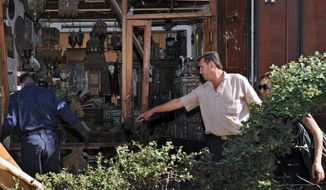 Syrians investigate an antiques shop damaged in a suicide bombing near the Greek Orthodox Virgin Mary Church in the predominantly Christian neighborhood of Bab Sharqi in central Damascus, Syria, on Thursday, June 27, 2013. (AP Photo/SANA)