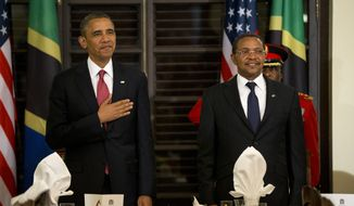 **FILE** President Obama and Tanzanian President Jakaya Kikwete stand for the national anthem during an official dinner at the State House in Dar es Salaam, Tanzania, on Monday, July 1, 2013. Mr. Obama was in Tanzania on the final leg of his three-country tour in Africa. (Associated Press)