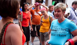 ** FILE ** Anti-abortion activist Pamela Whitehead (right) of Katy, Texas, argues with a pro-choice activist during the first day of hearings on House Bill 2 and Senate Bill 1 at the Texas Capitol in Austin on Tuesday, July 2, 2013. Activists of both sides attended the hearings in order bear testimony about the bills, which are aimed at restricting abortions across the state. (AP Photo/The Daily Texan, Guillermo Hernandez Martinez)