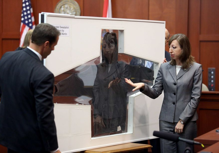 ** FILE ** Amy Siewert, a firearms expert with the Florida Department of Law Enforcement, faces the jury as Trayvon Martin's hooded sweatshirt is shown in Seminole circuit court, in Sanford, Fla., Wednesday, July 3, 2013. (AP Photo/Orlando Sentinel, Jacob Langston, Pool)