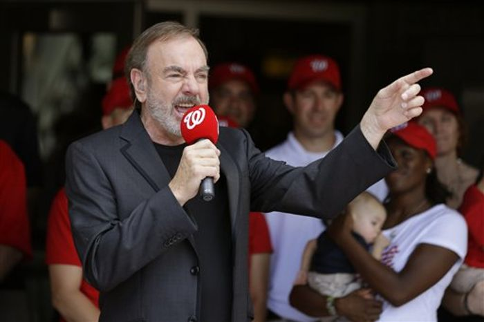 """Neil Diamond sings the """"Freedom Song (They'll Never Take Us Down),"""" after the third inning of a baseball game between the Washington Nationals and Milwaukee Brewers at Nationals Park Thursday, July 4, 2013, in Washington. It was Diamond's first live performance of the song, which was inspired by his visit to Boston in the days following the marathon bombings. (AP Photo/Alex Brandon)"""