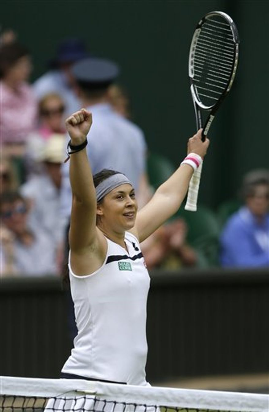 Marion Bartoli of France reacts after defeating Kirsten Flipkens of Belgium during their Women's singles semifinal match at the All England Lawn Tennis Championships in Wimbledon, London, Thursday, July 4, 2013. (AP Photo/Alastair Grant)