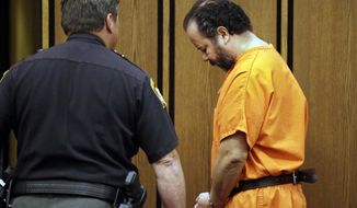 Ariel Castro is led back to jail after a hearing in Cuyahoga County Common Pleas Court in Cleveland, Wednesday, July 3, 2013. Castro is accused of holding three women captive for nearly a decade. (AP Photo/Mark Duncan)