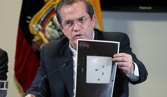 Ecuador's Foreign Minister Ricardo Patino holds up a photograph of what he says is the electric socket at his country's embassy in London where a hidden microphone was found, during a press conference in London in Quito, Ecuador, Wednesday, July 3, 2013. Patino said that two weeks ago a hidden microphone was found where Wikileaks founder and publisher Julian Assange is holed up. (AP Photo/Dolores Ochoa)