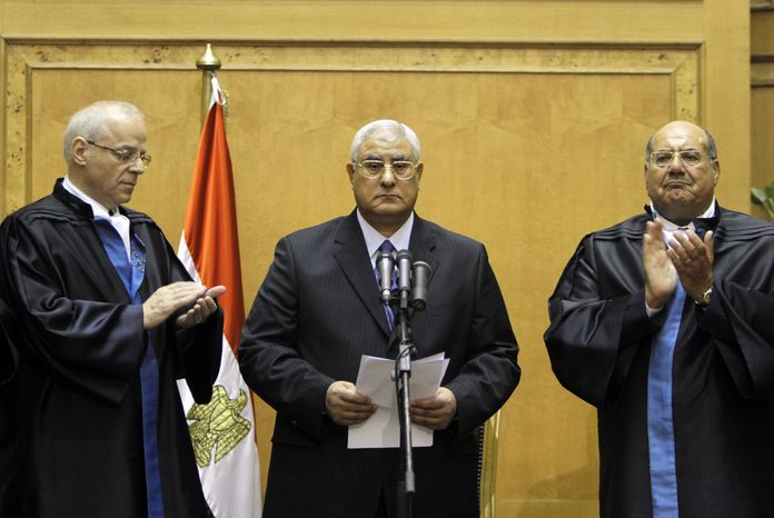 Egypt's chief justice Adly Mansour, center, is applauded by chiefs of the constitutional court after he is sworn in as the nation's interim president Thursday, July 4, 2013. The chief justice of Egypt's Supreme Constitutional Court was sworn in Thursday as the nation's interim president, taking over hours after the military ousted the Islamist President Mohammed Morsi. (AP Photo/Amr Nabil)