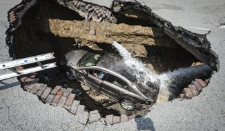 This photo provided by the Toledo, Ohio Fire and Rescue Department shows a car at the bottom of a sinkhole caused by a broken water line in Toledo, Ohio, on Wednesday, July 3, 2013. Police say the driver, 60-year-old Pamela Knox of Toledo, was shaken up and didn't appear hurt but was taken to a hospital as a precaution. (AP Photo/Toledo, Ohio Fire and Rescue Department, Lt. Matthew Hertzfeld)