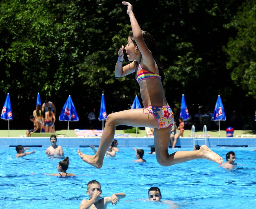A girl jumps into a swimming pool on a hot day in Skopje, Macedonia, on Wednesday, July 3, 2013, as the temperature reaches 30C (86F). Global warming accelerated since the 1970s and broke more countries' temperature records than ever before in the first decade of the new millennium, U.N. climate experts said Wednesday. (AP Photo/Boris Grdanoski)