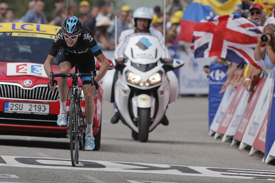 A fan waves a British flag as new overall leader Christopher Froome of Britain sprints towards the finish line to win the eight stage of the Tour de France cycling race over 195 kilometers (122 miles) with start in Castres and finish in Ax 3 Domaines, Pyrenees region, France, Saturday July 6 2013. (AP Photo/Laurent Cipriani)