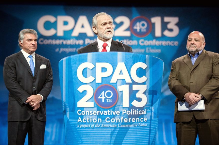 Washington Times President and CEO Larry Beasley announces the newspaper's straw poll results in March at the CPAC conference near Washington. He is joined by American Conservative Union Chairman Al Cardenas (left) and pollster Tony Fabrizio. (The Washington Times)