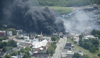 Smoke rises from burning railroad cars carrying crude oil after they derailed in downtown Lac Megantic, Quebec, on Saturday, July 6, 2013. A large swath of the town was destroyed, and up to 1,000 people were forced to evacuate. (AP Photo/The Canadian Press, Paul Chiasson)