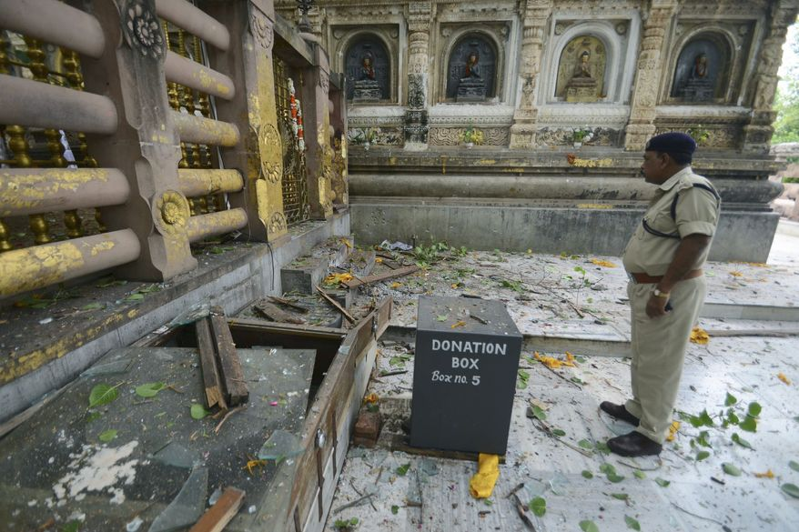 A security officer inspects the site of an explosion on the campus of the Mahabodhi Temple, the Buddhist Great Awakening temple, in Bodhgaya, about 80 miles south of Patna, the capital of the eastern Indian state of Bihar, on Sunday, July 7, 2013. A series of small blasts injured at least two people, police said. (AP Photo/Manish Bhandari)