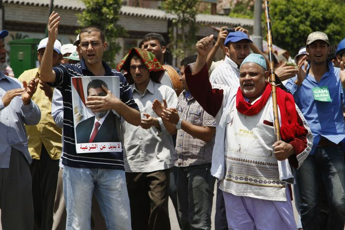 Supporters of ousted Egyptian President Mohammed Morsi chant slogans at a sit-in in Nasser City, a suburb of Cairo, on Sunday, July 7, 2013. (AP Photo/Paul Schemm)