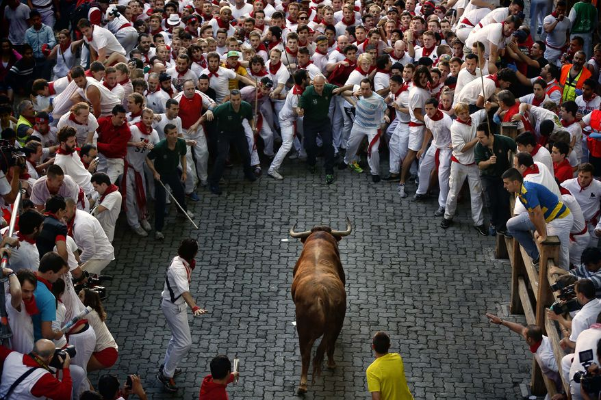 """A fighting bull runs toward revelers during the running of the bulls at the San Fermin festival in Pamplona, Spain, on Sunday, July 7, 2013. Revelers from around the world arrive in the city every year to take part on some of the eight days of the running of the bulls, glorified by Ernest Hemingway's """"The Sun Also Rises."""" (AP Photo/Daniel Ochoa de Olza)"""