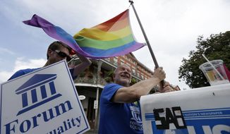 **FILE** John Hill (right), chairman of the Forum For Equality in Louisiana, waves a rainbow flag at a celebration rally in Jackson Square in New Orleans on June 26, 2013, after two Supreme Court decisions supporting gay rights were handed down. (Associated Press)
