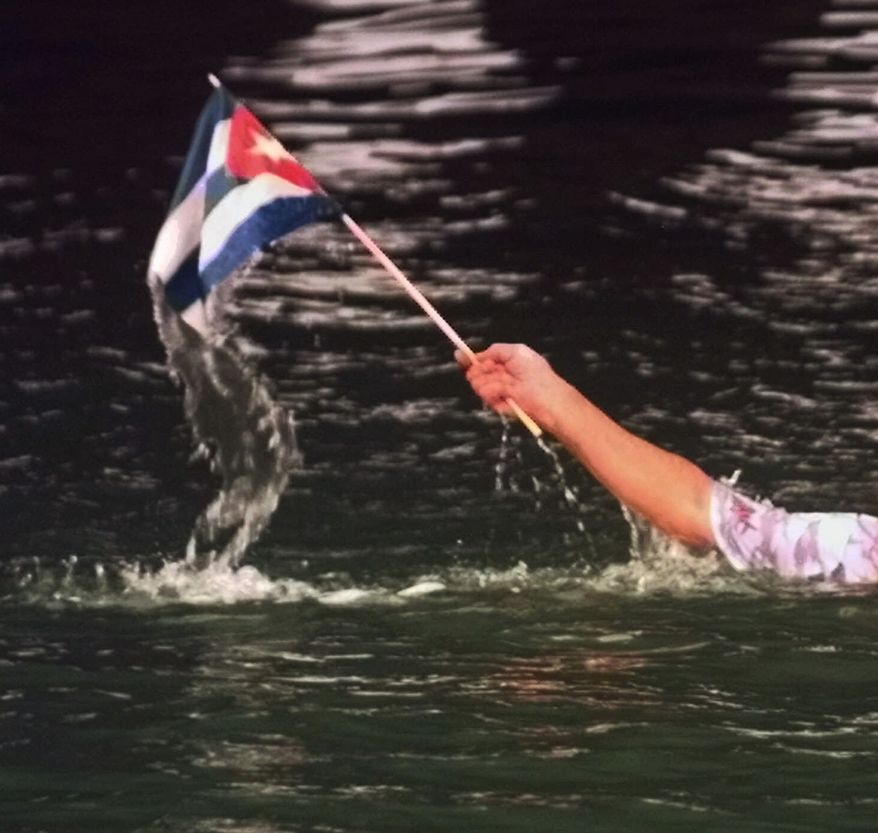 **FILE** Miguel Angel Concheso waves a Cuban flag after he jumped from the MacArthur Causeway leading to Miami Beach, Fla., on June 29, 1999 near the Miami Beach U.S. Coast Guard Station. Concheso was one of a group protesting the treatment of six Cuban refugees caught in Surfside, Fla., after two made it to shore and four others were caught in the water. Under U.S. policy, Cubans who reach American shores are allowed to stay and eventually get work permits, but those found at sea, even a few yards offshore, are usually returned to Cuba. (Associated Press)