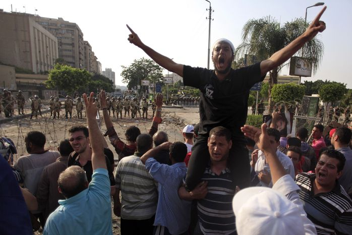 Supporters of ousted President Mohammed Morsi protest in front of the Republican Guard headquarters in Nasr City in Cairo on July 8, 2013. Egyptian soldiers and police opened fire on supporters of the ousted president in violence that left dozens of people killed, including one officer, outside a military building in Cairo where demonstrators had been holding a sit-in, government officials and witnesses said. (Associated Press)
