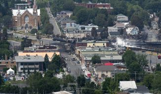 Burned-out railroad tanker cars and the smouldering remains of businesses in downtown of Lac-Megantic, Quebec, are seen on Sunday, July 7, 2013. A runaway train on Saturday derailed, igniting explosions and fires that destroyed the town's business district. (AP Photo/The Canadian Press, Paul Chiasson)