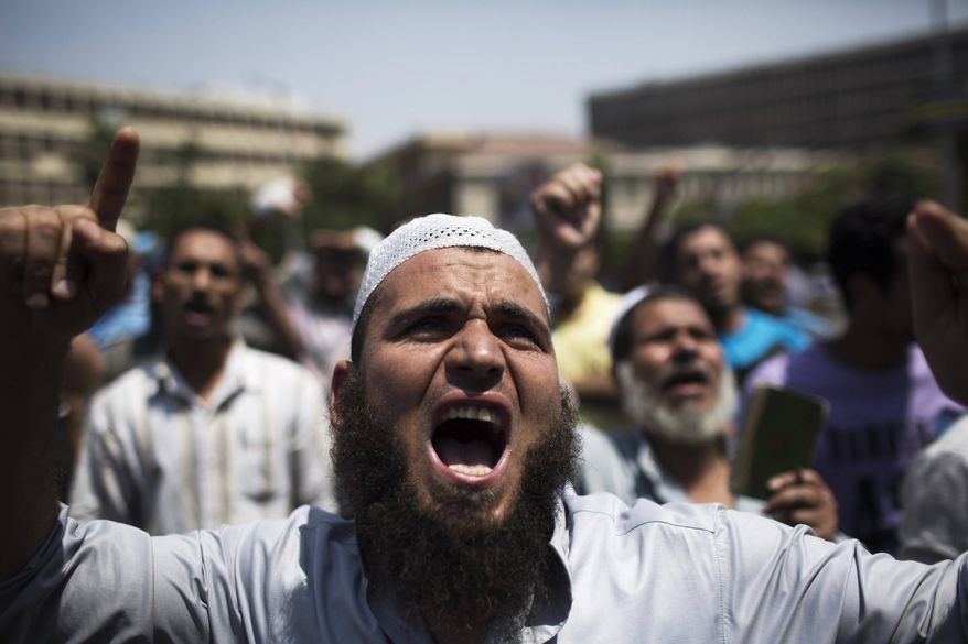 Supporters of Egypt's ousted President Mohammed Morsi chant slogans against the military near Cairo University, where protesters have installed their camp in Giza, southwest of Cairo, Egypt, Monday, July 8, 2013. (AP Photo/Manu Brabo)