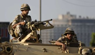 Egyptian army soldiers take their positions on top of their armored vehicle to guard the entrances of Tahrir square, in Cairo, Egypt, Monday, July 8, 2013. Egyptian military officials said gunmen killed at least five supporters of the former president when people tried to storm a military building in Cairo. (AP Photo/Hassan Ammar)