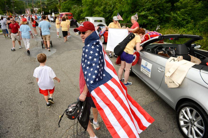 Rob Kaler of Washington, D.C., center, drapes himself in an American Flag and walks past parade vehicles as the Palisades July 4th Parade gets ready to begin, Washington, D.C., Thursday, July 4, 2013. (Andrew Harnik/The Washington Times)