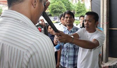 In this photo taken July 7, 2013, Chidchai Utmacha, right, a Thai taxi driver shows how he stabbed an American passenger, Troy Lee Pilkington, during a police re-enactment in Bangkok, Thailand. (AP Photo)