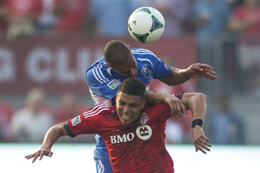 Toronto FC 's Luis Silva, bottom, battles for the ball with Montreal Impact's Matteo Ferrari during first-half MLS soccer game action in Toronto, Wednesday, July 3, 2013. (AP Photo/The Canadian Press, Chris Young)