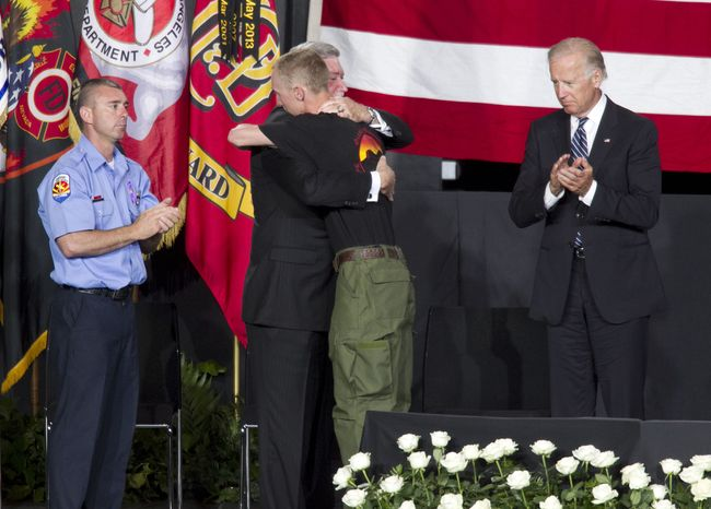 """Brendan McDonough (center right), the sole surviving member of the Granite Mountain Hotshots crew, hugs Harold A. Schaitberger, general president of the International Association of Firefighters, as Vice President Joseph R. Biden and Dan Bates, Prescott Chapter Vice President of United Yavapai Firefighters Association, Local 3066, look on during the """"Our Fallen Brothers"""" memorial service for the 19 fallen firefighters at Tim's Toyota Center in Prescott Valley, Ariz., on Tuesday, July 9, 2013. (Associated Press/The Arizona Republic)"""