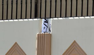 This photo was taken on Thursday, June 20, 2013, shows the Taliban flag visible through a gap in a wall of the new office of the Afghan Taliban in Doha, Qatar, after the opening of the office several days ago. (AP Photo/Osama Faisal)
