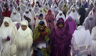"Muslim women perform an evening prayer called ""tarawih,"" marking the first eve of the holy fasting month of Ramadan, at a mosque in Denpasar, Bali, Indonesia, on Tuesday, July 9, 2013. During Ramadan, the holiest month in Islamic calendar, Muslims refrain from eating, drinking, smoking and sex from dawn to dusk. Fasting during Ramadan is one of the Five Pillars of Islam. (AP Photo/Firdia Lisnawati) ** FILE **"
