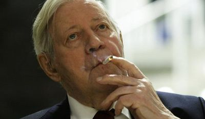 **FILE** Germany's former Chancellor Helmut Schmidt smokes a cigarette prior to the opening of a photo exhibition about Schmidt in Berlin on Dec. 17, 2008. (Associated Press)