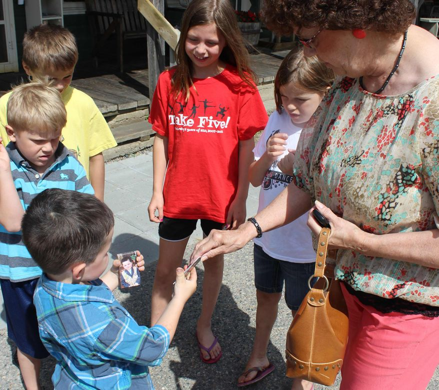 "Robert ""Bobby"" Tufts, the 4-year-old mayor of Dorset, Minn., hands his card to potential voters on Wednesday, June 26, 2013, in his campaign for re-election. (AP Photo/Jeff Baenen)"