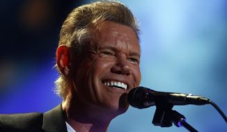 In this June 7, 2013 photo, Randy Travis performs at the CMA Music festival in Nashville. The 54-year-old singer is recovering from brain surgery after suffering a stroke while he was being treated for congestive heart failure because of a viral illness. (Photo by Wade Payne/Invision/AP, File)