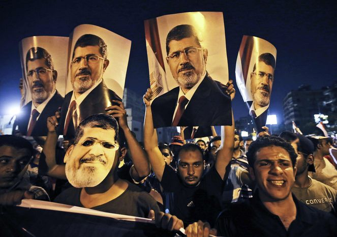 ** FILE ** In this Wednesday, July 10, 2013, photo, supporters of ousted Egypt's President Mohammed Morsi hold posters of him as they protest during the Islamic month of Ramadan, in Nasr City, Cairo, Egypt. (AP Photo/Hussein Malla)